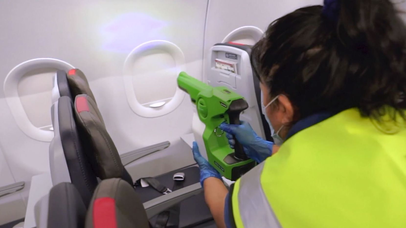 A cleaning worker uses an electrostatic sprayer to apply an antimicrobial product on an American Airlines jet. The product, called SurfaceWise2 and made by Allied BioScience, got EPA approval for inactivating the COVID-19 virus on surfaces for up to 7 days.