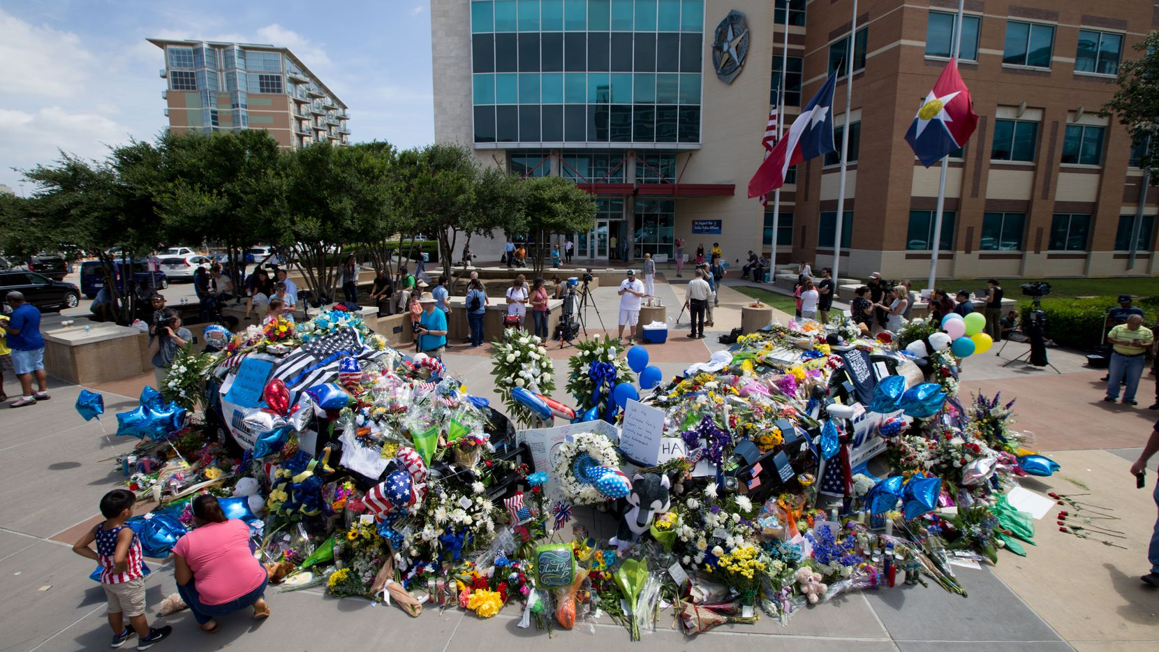By July 9, two Dallas police cars were buried so deep in flowers and mementos that they could no longer be seen, as a memorial for the injured and slain officers from the July 7 shooting slowly grew bigger in front of Dallas police headquarters.