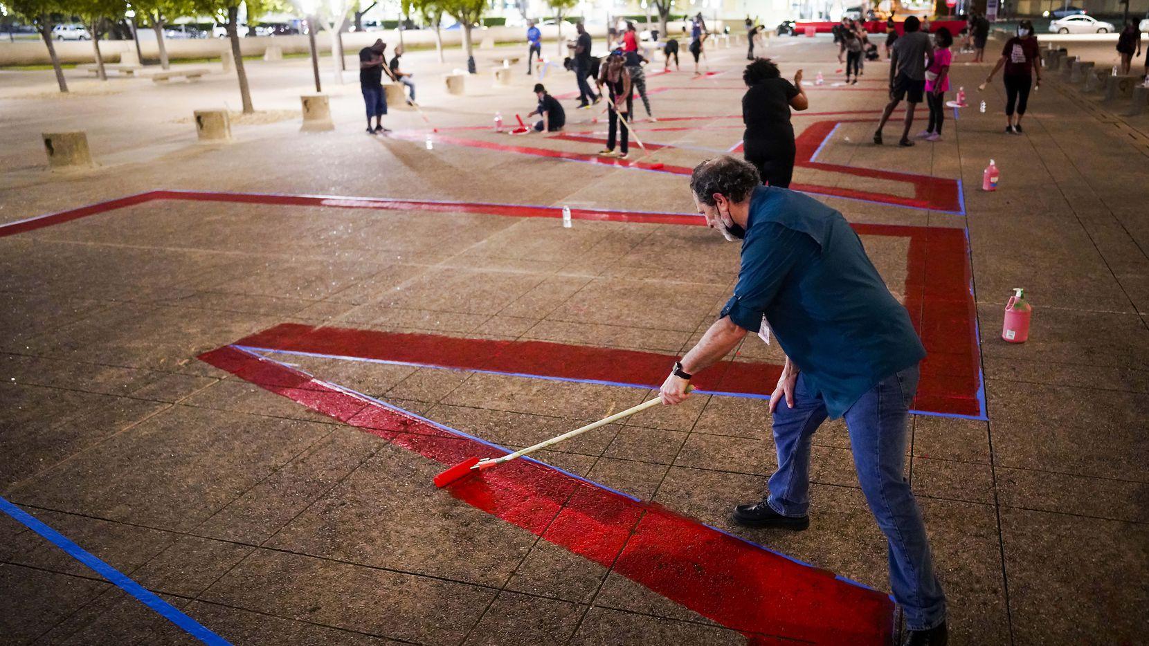 """El concejal Lee Kleinman ayuda a pintar un gran mensaje con la consigna """"Black Lives Matter"""" en la plaza de la alcaldía de Dallas la noche del lunes 8 de junio de 2020."""