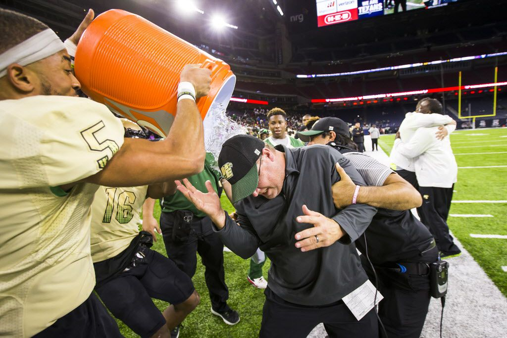 DeSoto head coach Todd Peterman  is doused with water by defensive back Byron Hanspard Jr. (5) and linebacker Ashton Brooks (16) after a victory over Klein Collins in a UIL Class 6A Division II state semifinal playoff football game at NRG Stadium on Saturday, Dec. 10, 2016, in Houston. (Smiley N. Pool/The Dallas Morning News)