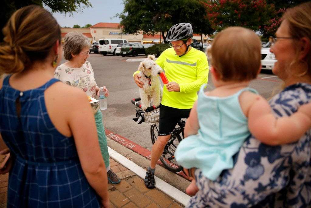 Paul Gore feeds his dog Nigel a popsicle as they make a stop on their bike ride.  Joining him was (from left) Melanie Yearta, daughter Whitney Bailey, grand daughter Emma Bailey and Tammy Gore. The East Dallas community showed support for businesses in Casa Linda Plaza shopping center following a controversial decision to remove historic trees to make way for more parking in Dallas, Friday, July 27, 2018.