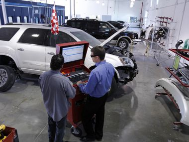 Technician Tad Waymire (left) works with Troy Ash, body shop manager at Caliber Collision Centers' new location in Keller.