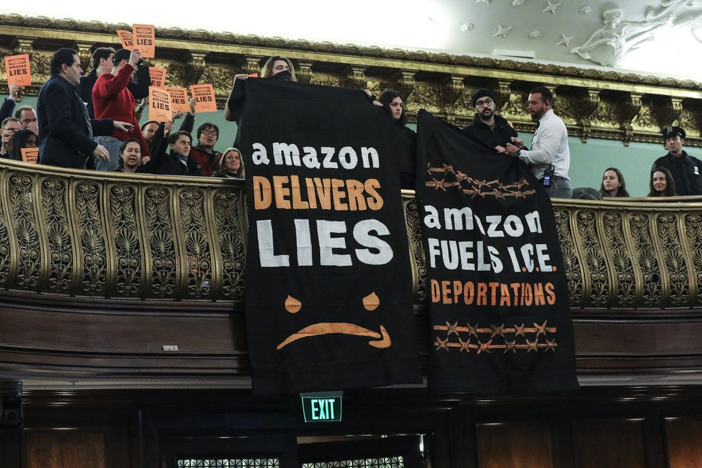 Protesters unfurl anti-Amazon banners from the balcony of a hearing room during a New York City Council Finance Committee hearing, revealing why New York is losing out to other states.