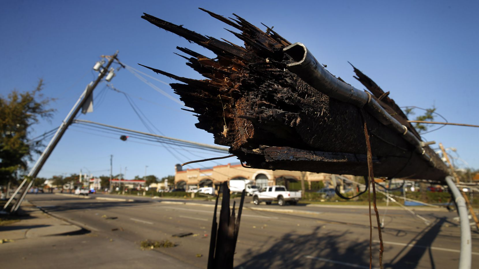 A sheared off utility pole lays over Preston Rd in Dallas near the Preston Royal shopping center Monday, October 21, 2019. A tornado tore through the entire neighborhood knocking down trees and ripping roofs from homes and businesses.