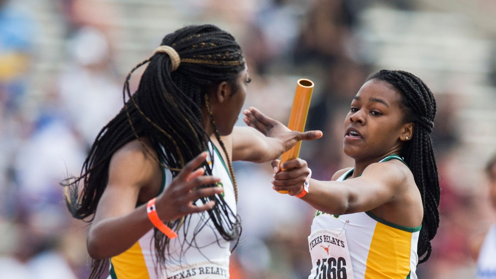 DeSoto's Trinity Kirk (right) hands off the baton to Rosaline Effiong (left) during the High School Girls 1600 Meter Sprint Medley Relay at Texas Relays track and field meet on Friday, March 29, 2019 at Mike A. Meyers Stadium at the University of Texas in Austin.
