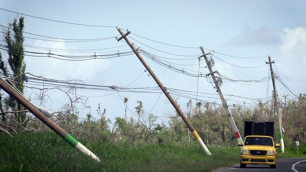 Power poles lean precariously along Highway 118 near San Isidro, Puerto Rico. About 86 percent of the island still doesn't have power about a month after Hurricane Maria struck.