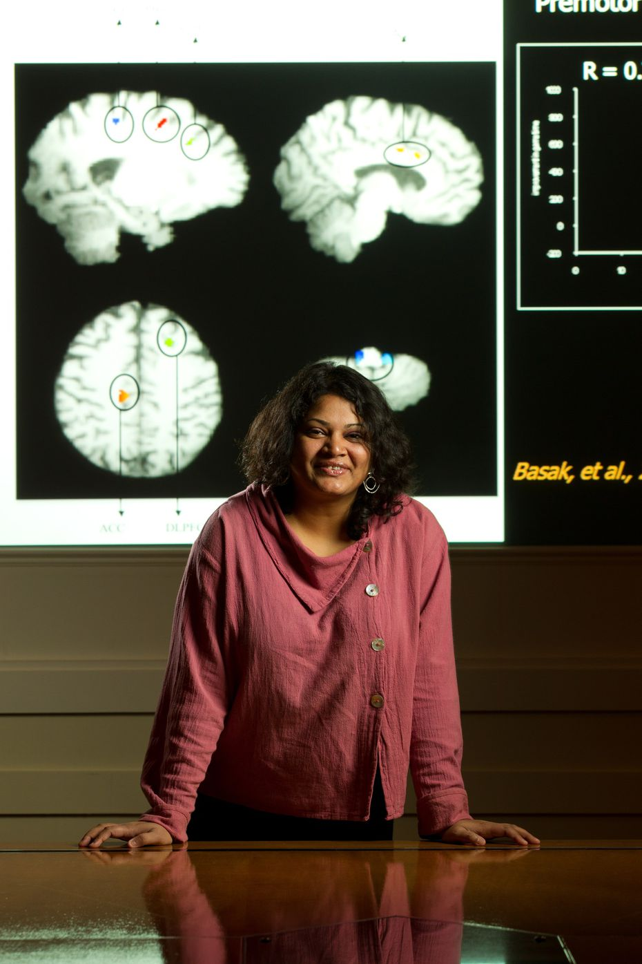 Chandramallika Basak, a cognitive neuroscientist at UT-Dallas, poses for a portrait in front of images of brain scans. Though Basak couldn't conduct brain scans this summer, she was still able to collect psychological data from participants in her brain-training study.