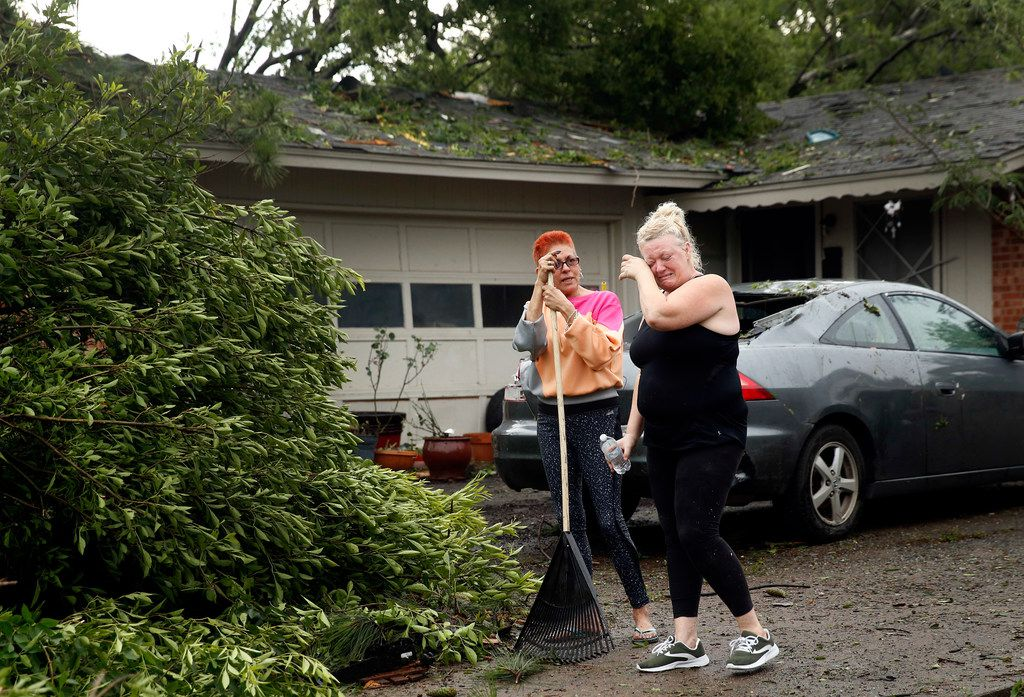 Resident Peggy Pierson (right) wipes away tears as she and her roommate Penny Ruiz cleanup parts the the trees that fell on their rental house on Andrews St. in North Arlington, Sunday, June 16, 2019. High winds from a thunderstorm toppled trees in the neighborhood near Globe Life Park.