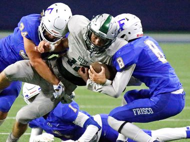 Reedy High School wide receiver Karston Farragut (17) is tackled by Frisco High School linebacker John Willis (34)  and Frisco High School defensive back Trent Bryant (8) during the first half as Reedy High School hosted Frisco High School in a district 7-5A football game at the Ford Center in Frisco on Friday, September 27, 2019.