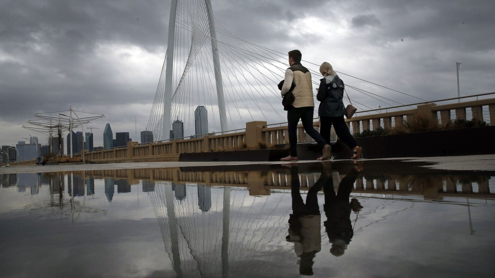 As clouds from a passing shower move across the Dallas skyline and the Margaret Hunt Hill Bridge, Michael McKinney and Maddi Reid of Dallas take a stroll across the Continental Street Bridge in Dallas on the their fourth wedding anniversary, Friday, January 10, 2020. (Tom Fox/The Dallas Morning News)