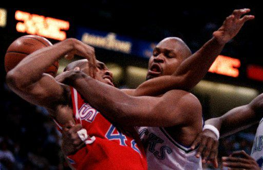2/27/96--The Mavericks' Terry Davis gets  tangled up with The Philadelphia 76ers' Jerry Stackhouse during  the first quarter of their game at Reunion Arena. Photographer: William Snyder /The Dallas Morning News
