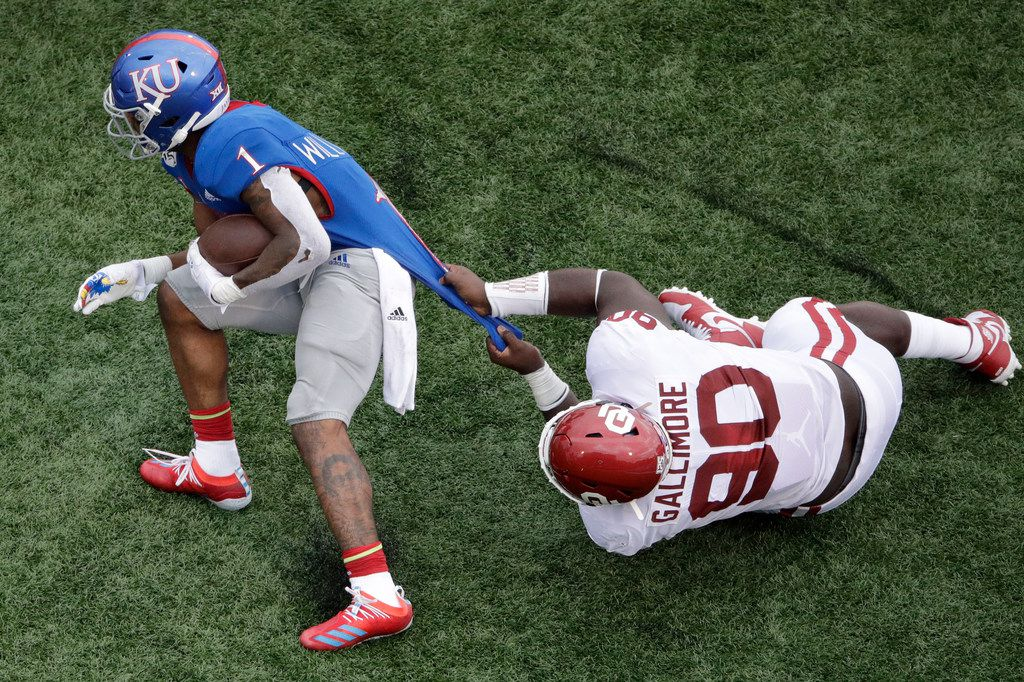 Oklahoma defensive lineman Neville Gallimore (90) tackles Kansas running back Pooka Williams Jr. (1) during the first half of an NCAA college football game Saturday, Oct. 5, 2019, in Lawrence, Kan. (AP Photo/Charlie Riedel)