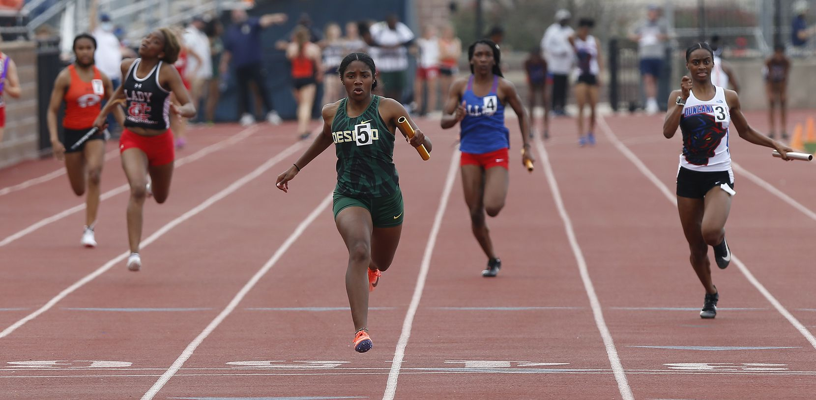 Mia Abraham (center) crosses the finish line first for DeSotto High School in the girls 4x100 at the Jesuit-Sheaner Relays held at Jesuit College Preparatory School in Dallas on Saturday, March 27, 2021.  (Stewart F. House/Special Contributor)