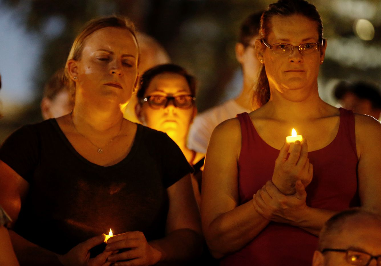 Leslie Decker (left) and Ashley Sheets attend a candlelight vigil in remembrance of Heather Heyer at Lee Park in Dallas on Sunday.
