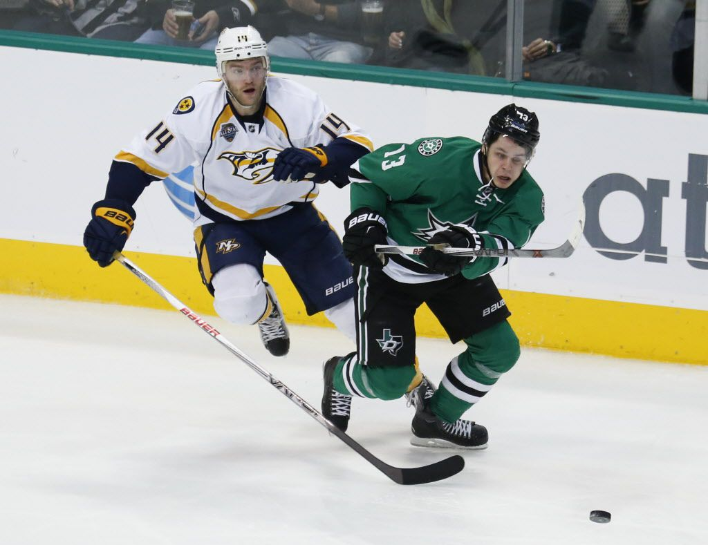 Dallas Stars center Mattias Janmark (13) and Nashville Predators defenseman Mattias Ekholm (14) chase the puck during the third period of an NHL hockey game, Thursday, Dec. 31, 2015, in Dallas. The Stars won 5-1. (AP Photo/Jim Cowsert)