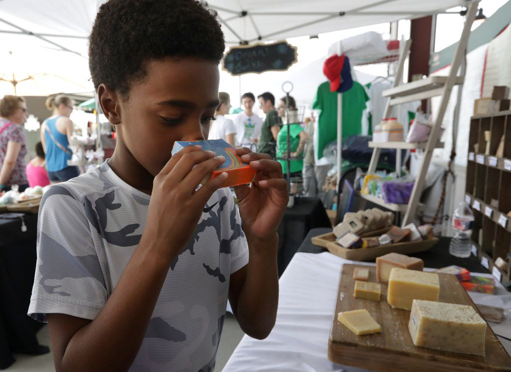 Ten-year-old Josh Johnson smells a sample soap at the Organik Junkie Soap & Co. booth during the Frisco Fresh Market.
