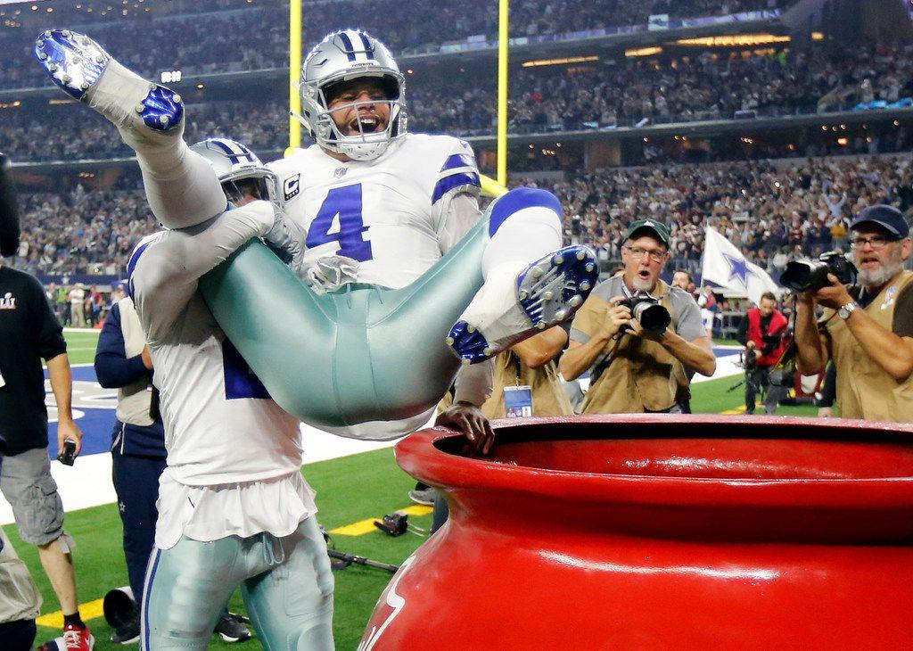Dallas Cowboys running back Ezekiel Elliott (21) throws quarterback Dak Prescott (4) into the Salvation Army kettle after Dak scored a fourth quarter touchdown against the Washington Redskins at AT&T Stadium in Arlington, Texas, Thursday, November 22, 2018. The Cowboys defeated the Redskins, 31-23. (Tom Fox/The Dallas Morning News)