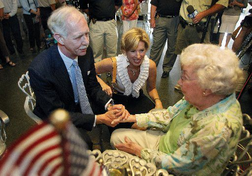"""Capt. Chesley """"Sully"""" Sullenberger (left) and his wife, Lorrie (center), greet Evelyn Cook of Sherman, whose husband LT Cook, Jr. taught Capt. Sullenberger to fly. Sullenberger was greeting people from his hometown at the Katy Depot in downtown Denison before a ceremony June 6, 2009."""