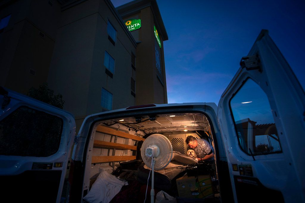 Jeff Slaughter holds his dog Triton in the back of a U-Haul van on Wednesday, June 6, 2018, in Denton.