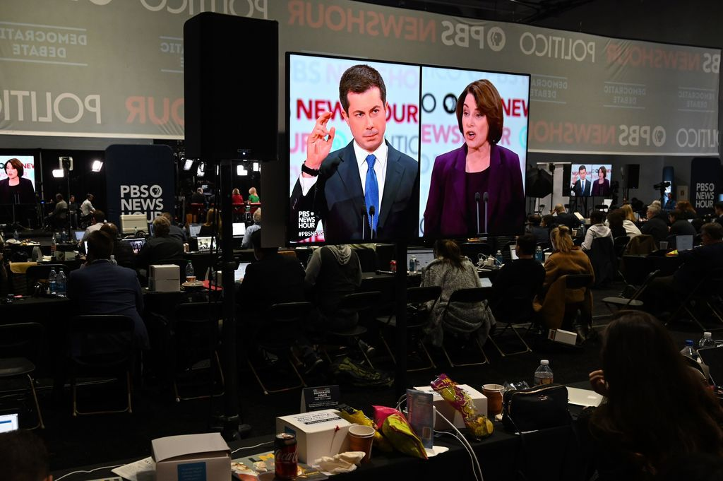 Pete Buttigieg and Amy Klobuchar are shown on screens in the spin room during the debate.