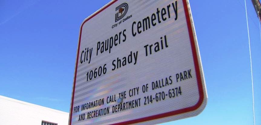 The small sign that marks the entrance to the cemetery off Shady Trail, which is tucked behind warehouses.