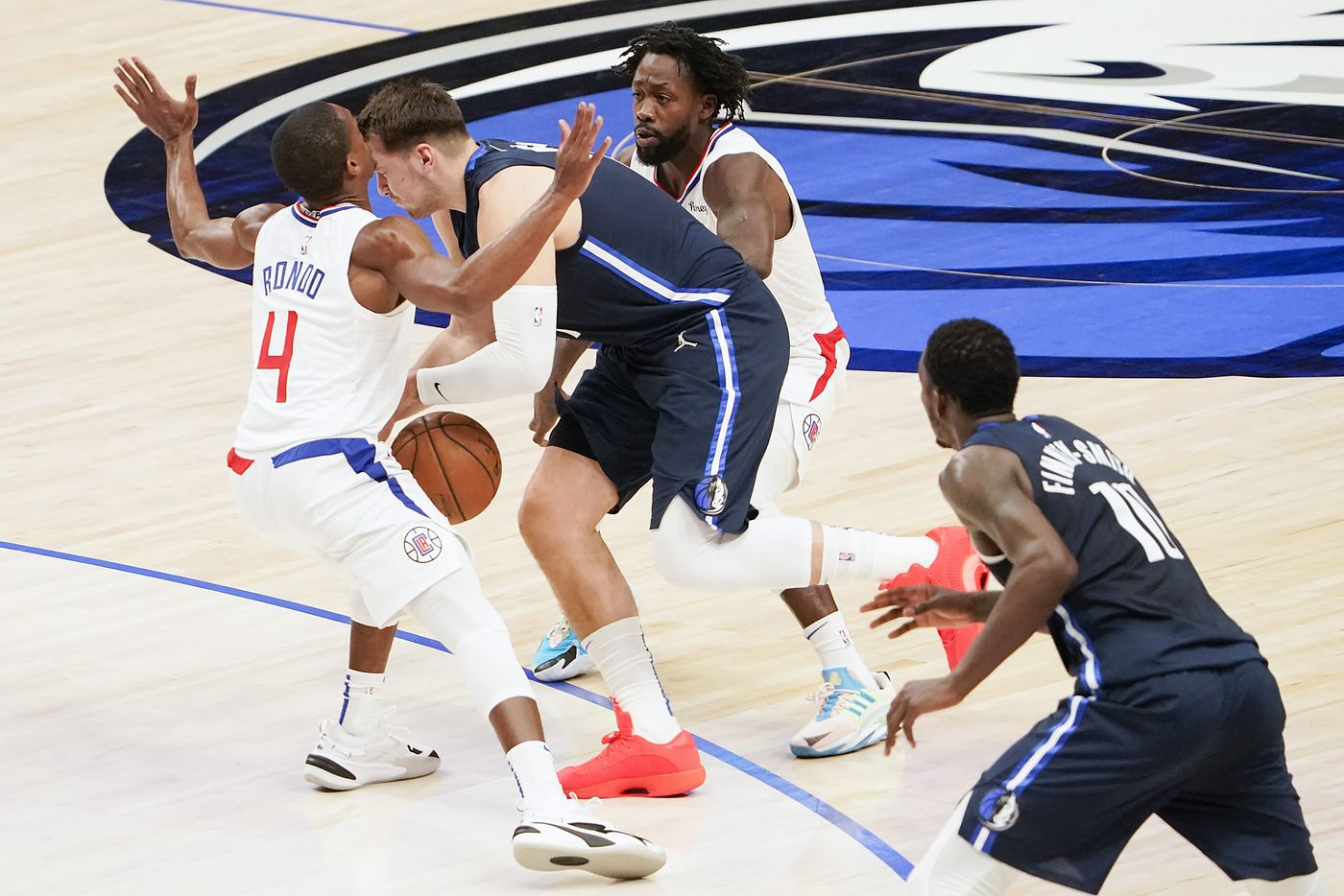 Dallas Mavericks guard Luka Doncic (77) collides with LA Clippers guard Rajon Rondo (4) as he gets past guard Patrick Beverley (21) during the first quarter of an NBA playoff basketball game at American Airlines Center on Friday, May 28, 2021, in Dallas. Doncic was called for a foul on the play.