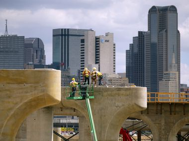Construction crews work atop the bridge support columns and tops of the new northbound Interstate 35E bridge leading to downtown Dallas, a part of the massive Dallas Horseshoe Project, Thursday, May 29, 2014. The nearly $800 million design-build project was worked on by Pegasus Link Contractors, the joint venture between Fluor Enterprises and Balfour Beatty Infrastructure.