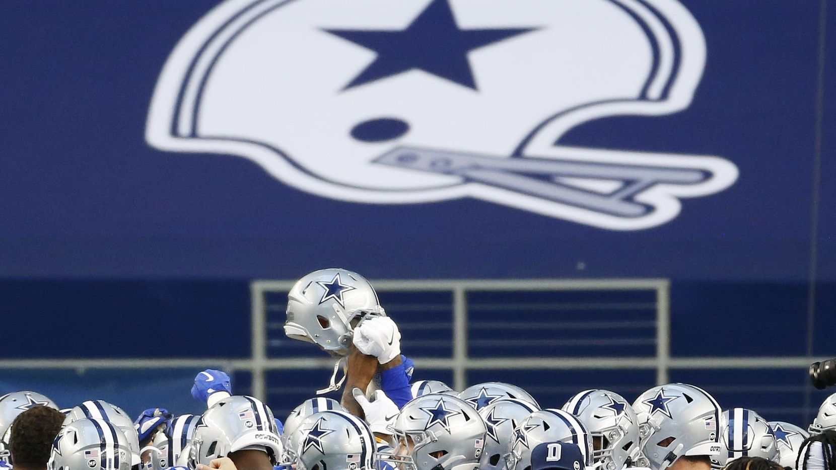 The Cowboys hoist a helmet after finishing warmups for a game against the 49ers at AT&T Stadium on Sunday, Dec. 20, 2020, in Arlington.