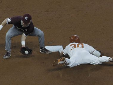 Texas Longhorns outfielder Eric Kennedy (30) safely steals 2nd base as Mississippi State 2nd baseman Scotty Dubrule (3) fields the throw and was late with the tag during the bottom of the first inning of play. The University of Texas baseball team locked horns with  Mississippi State for their opening round game in conjunction with the StateFarm College Baseball Showdown tournament held at Globe Life Field in Arlington on February 20, 2021. (Steve Hamm/ Special Contributor)