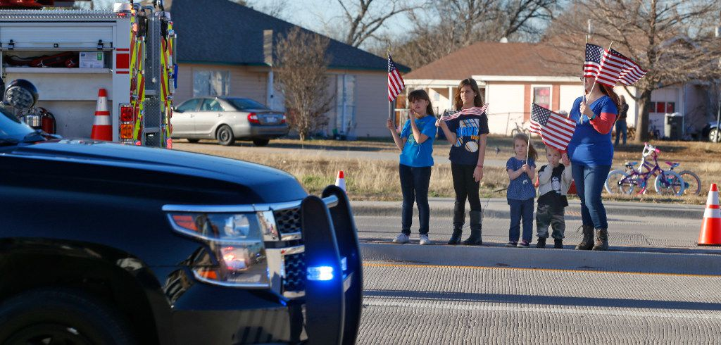 A family pays its respects on the procession route on Eldorado Pkwy for Det. Jerry Walker who was killed in the line of duty in Little Elm, Texas on January 23, 2017. (Nathan Hunsinger/The Dallas Morning News)