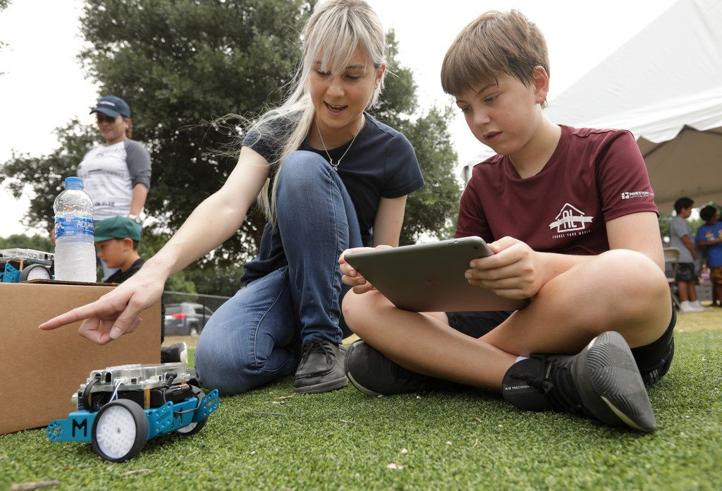 Meagan Coffer, left, and 11-year-old Ryan Martin program a robot during the Frisco Family Services Summer Lunch Grande Finale event at Bright Academy in Frisco, TX, on Aug. 2, 2019. (Jason Janik/Special Contributor)