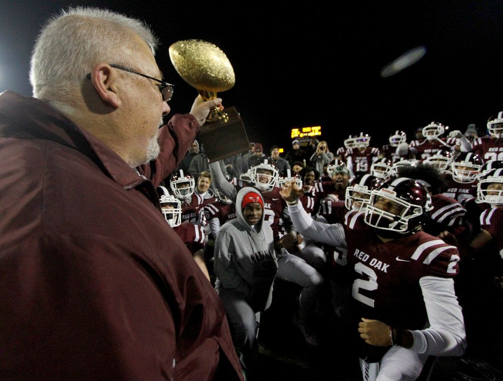 Red Oak ISD School Board President John Anderson presents the district trophy to members of the Red Oak hawks following their 48-13 victory over Seagoville. Anderson was a player on the 1982 championship hawks team which was the last time the football program won an outright district title trophy. The two teams played District 6-5A Division ll football game at Billy Goodloe Stadium in Red Oak on November 7, 2019. (Steve Hamm/ Special Contributor)