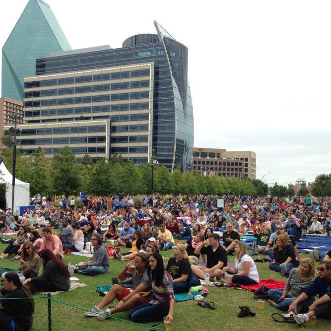 Visitors to Klyde Warren Park sit on the lawn for a free concert.