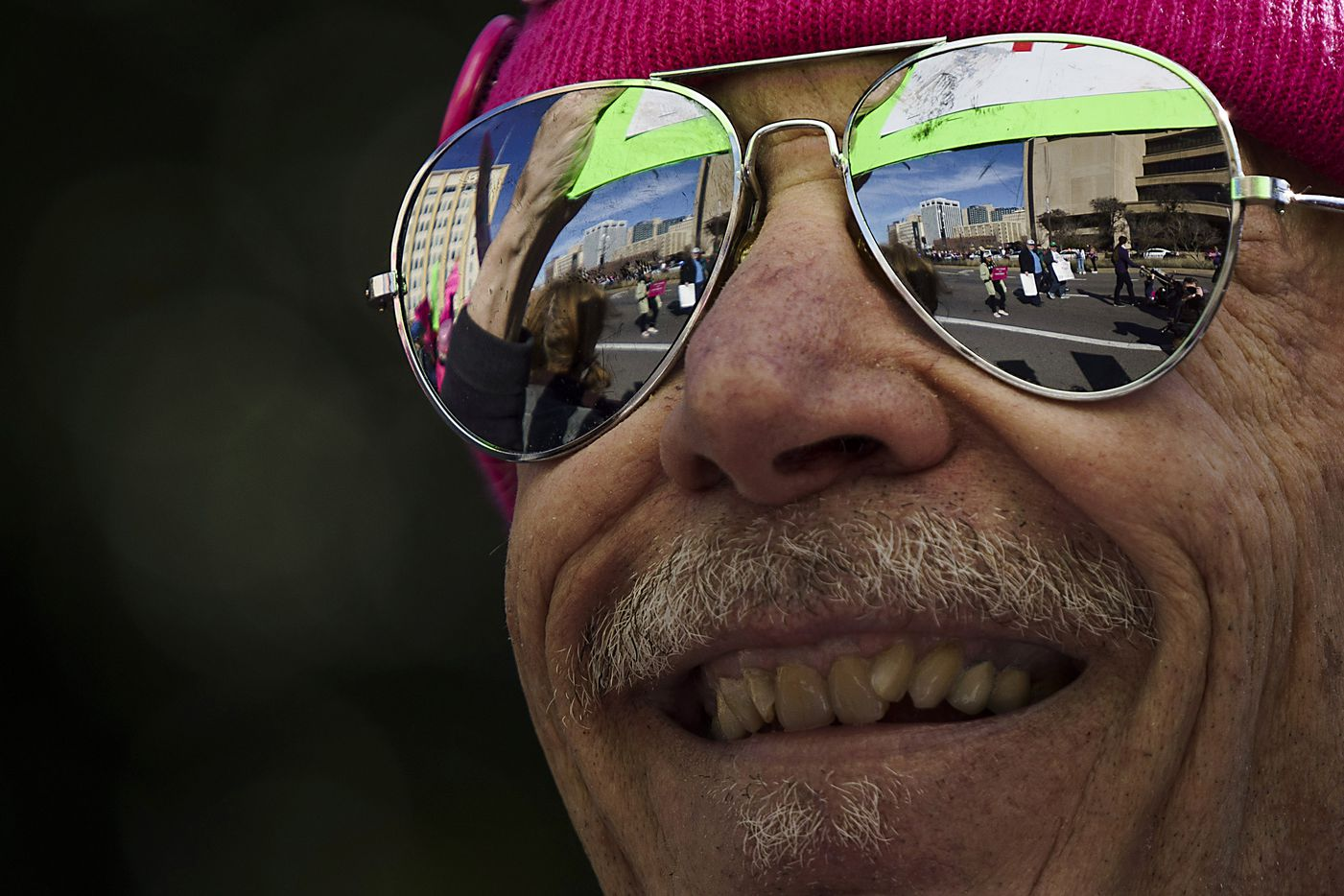 Participants in the 2020 Dallas Women's March are reflected in another demonstrators glasses as they walk along Canton Street on their way to a rally at Dallas City Hall on Sunday, Jan. 19, 2020, in Dallas.