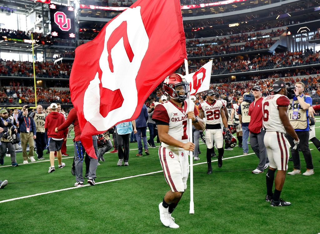 Oklahoma Sooners quarterback Kyler Murray runs around the field with the school flag after defeating the Texas Longhorns in the Big 12 Championship at AT&T Stadium in Arlington, Texas, Saturday, December 1, 2018. The Sooners defeated the Longhorns, 39-27. (Tom Fox/The Dallas Morning News)