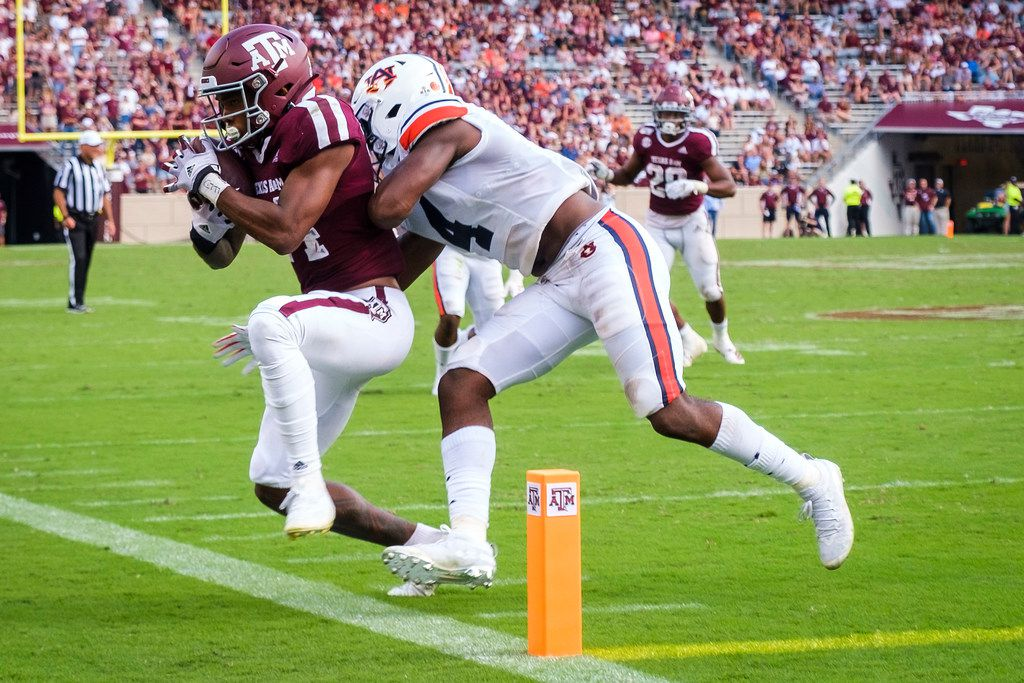 Texas A&M wide receiver Camron Buckley (14) is pushed out of bounds just short of the end zone by Auburn defensive back Noah Igbinoghene (4) during the second half of an NCAA football game at Kyle Field on Saturday, Sept. 21, 2019, in College Station, Texas.  The Aggies settled for a field goal on the drive. Auburn won the game 28-20.
