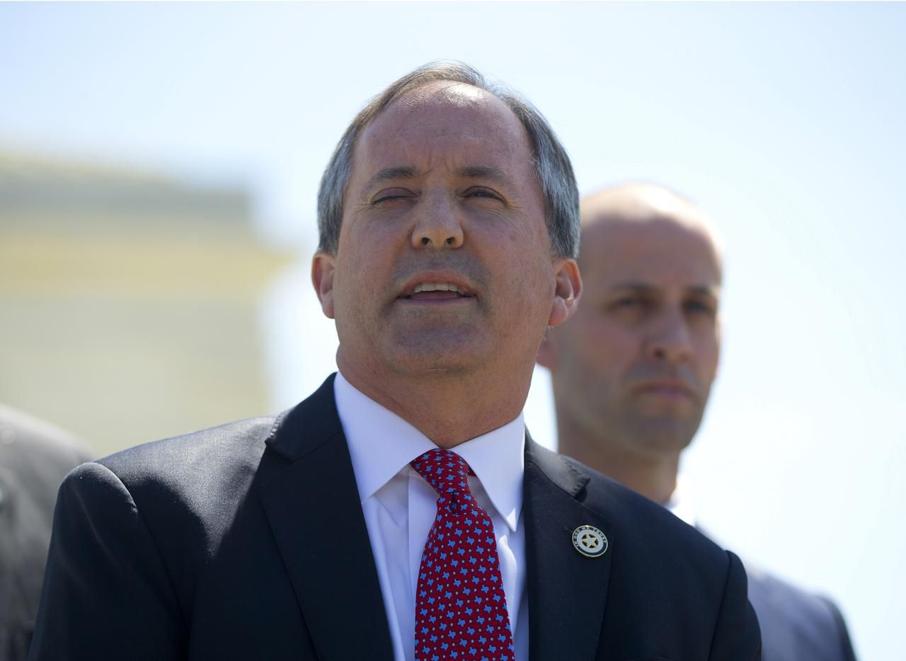 Texas Attorney General Ken Paxton, left, in Washington last month as the Supreme Court considered an important dispute over immigration.