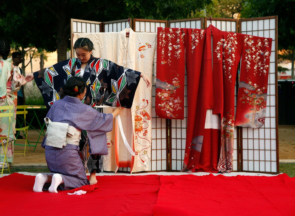 Yuki Takamatsu (standing) is dressed in a kimono by Sumiko Hashimoto during a demonstration at a previous Otsukimi festival in Dallas.