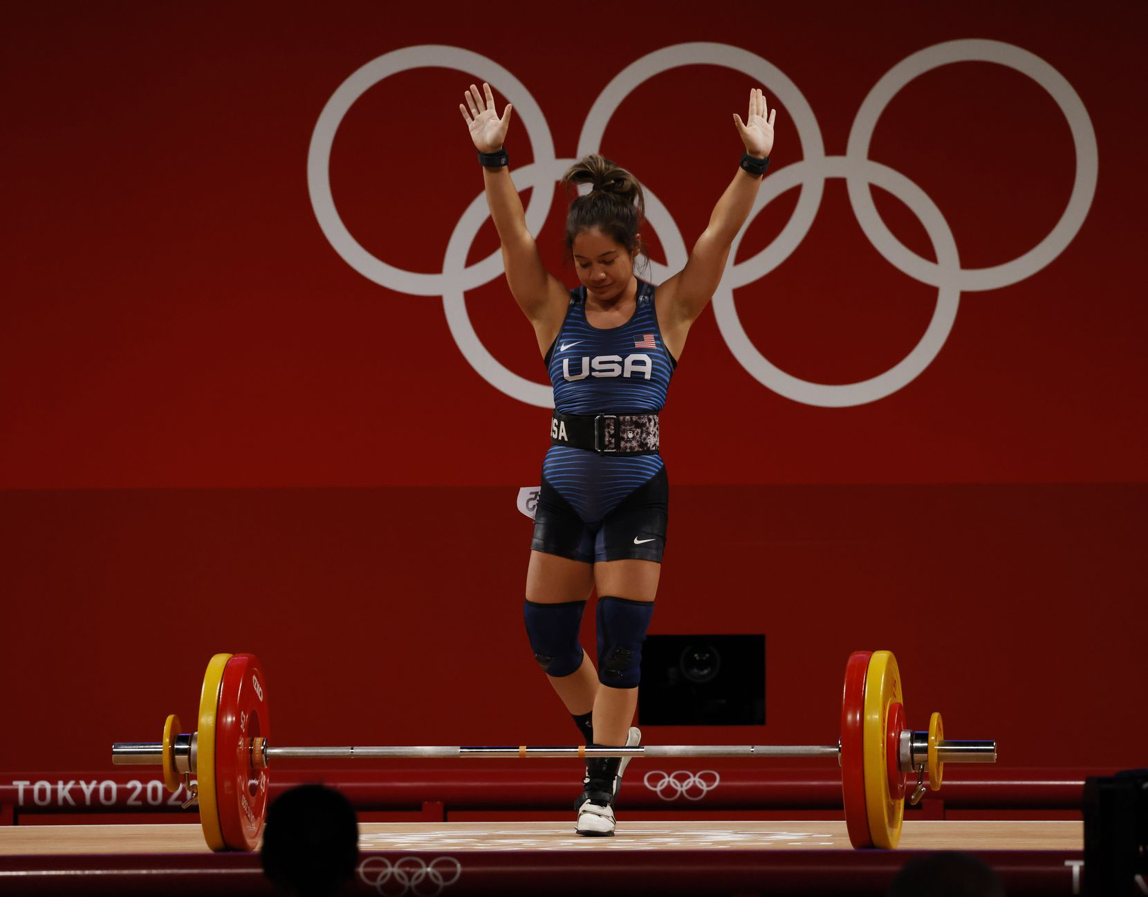 USA's Jourdan Delacruz waves after an unsuccessful attempt in lifting 108 kg on her third attempt in the clean and jerk round during the women's 49 kg weightlifting final during the postponed 2020 Tokyo Olympics at Tokyo International Forum on Saturday, July 24, 2021, in Tokyo, Japan. Delacruz received a no-lift on all three attempts of the clean and jerk round. (Vernon Bryant/The Dallas Morning News)