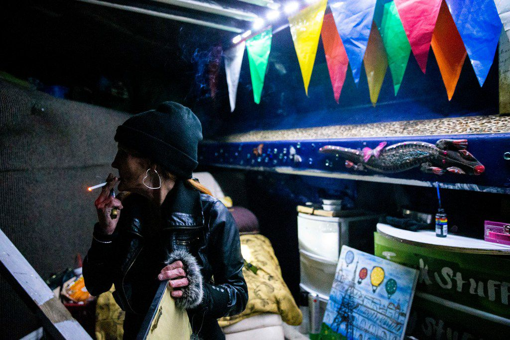 Kim Henderson smokes a cigarette in her encampment under an Interstate 35E bridge during the annual homeless count in Dallas on Thursday night.