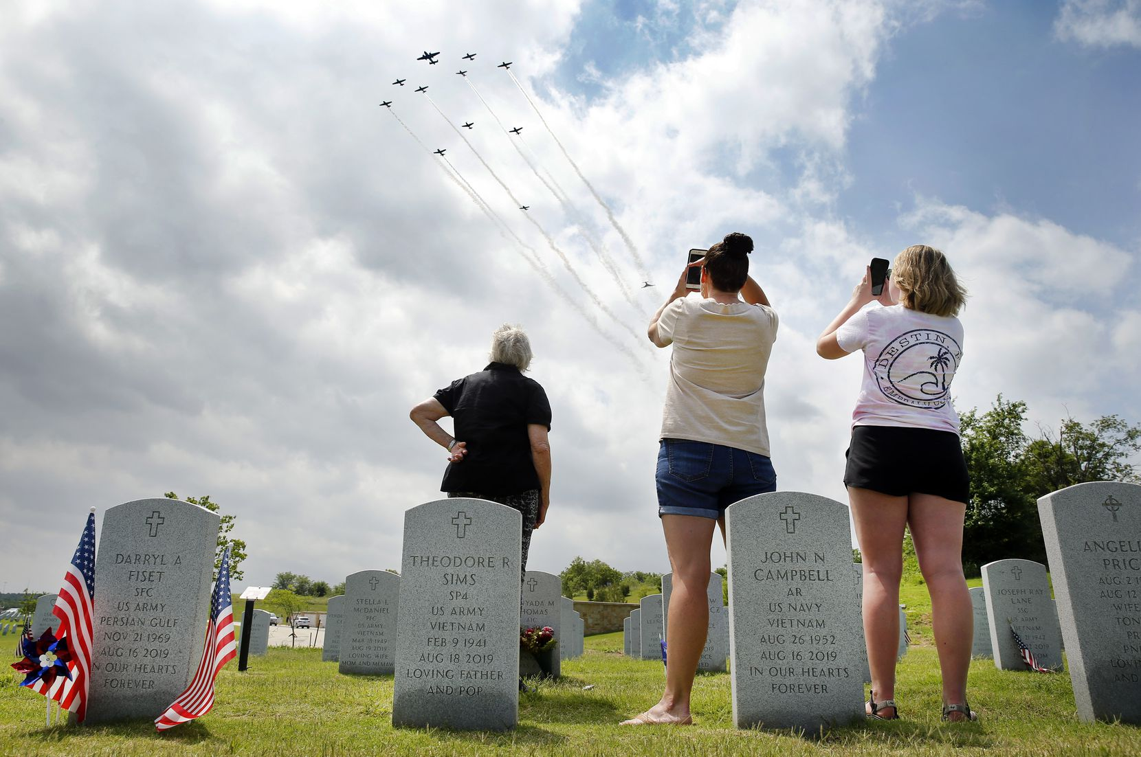 Three generations of the Wolniewicz family watched a group of old warplanes perform a flyover at Dallas-Fort Worth National Cemetery on May 22. From left are Carol Wolniewicz of Parker, daughter Krystal Kenney of Famersville and granddaughter Kandace Kenney, who came to visit the grave of Wolniewicz's husband, Vincent W. Wolniewicz, a retired Air Force officer who died last year.
