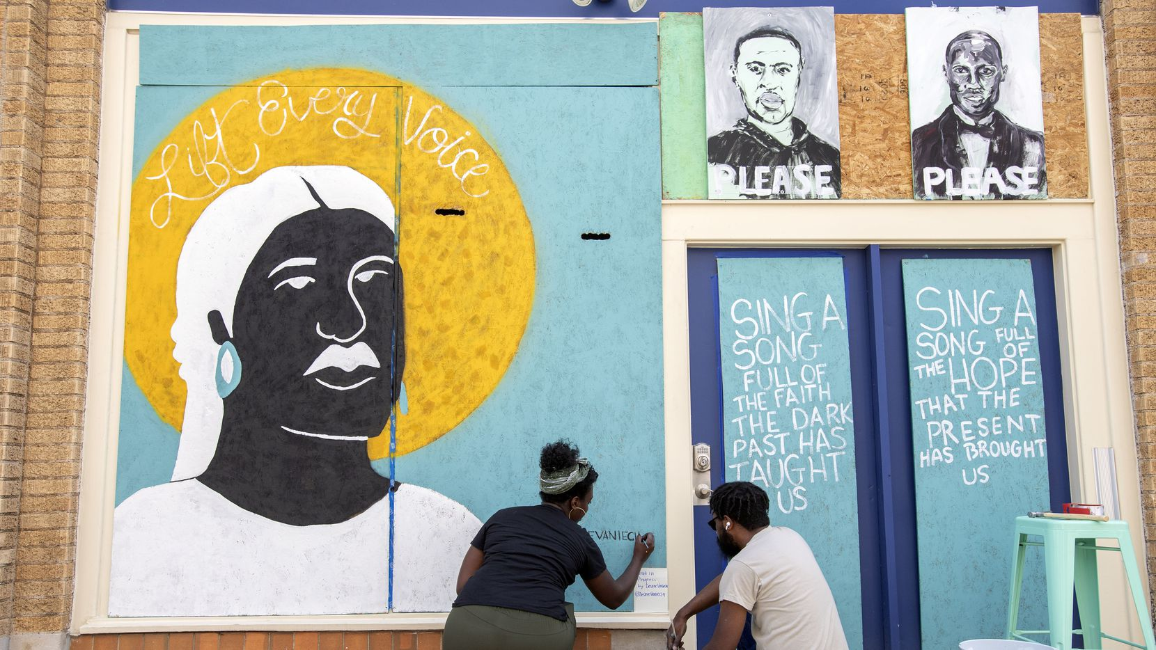 Desiree Vaniecia and Joeneal Berry sign their names on a mural they painted on plywood on Monday, June 1, 2020 in Deep Ellum in Dallas. Two other artworks, by Dallas artist Joel Murray, are also displayed above the doorway.
