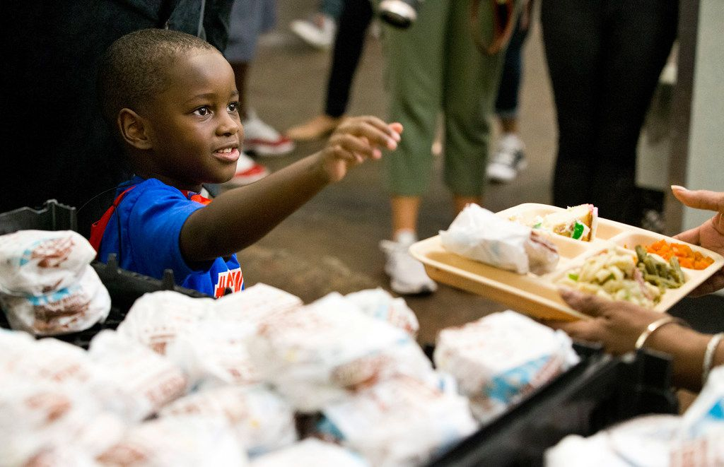 """President"" Austin Perine, 4, looked at a homeless person after handing him a sandwich Thursday at Dallas LIFE."