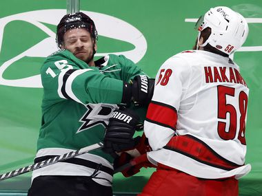 Carolina Hurricanes defenseman Jani Hakanpaa (58) slams Dallas Stars left wing Blake Comeau (15) into the boards during the first period at the American Airlines Center in Dallas, Tuesday, April 27, 2021.