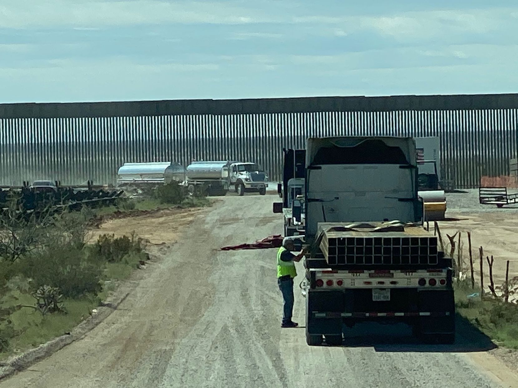 Truckers lined up near the wall construction site April 1 near Columbus, N.M. Truckers and other workers expressed mixed feelings about wall construction amid the coronavirus pandemic.