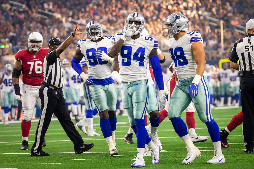 Dallas Cowboys defensive end Randy Gregory (94) celebrates with defensive end Tyrone Crawford (98) and defensive end Demarcus Lawrence (90) after a sack of Arizona Cardinals quarterback Sam Bradford during the first quarter of a preseason football game at AT&T Stadium on Sunday, Aug. 26, 2018, in Arlington, Texas. (Smiley N. Pool/The Dallas Morning News)