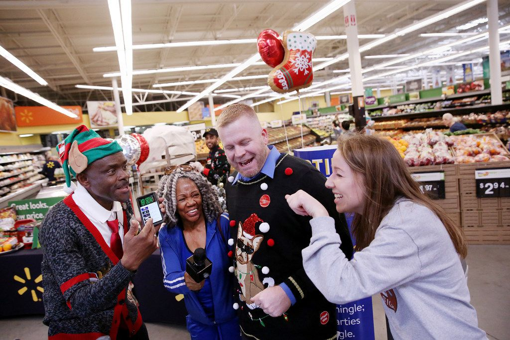 """From left: Augustin Folly, grocery department manager, customer Trish Means of Dallas, Kevin Newland, Fresh department assistant manager, and Lexi Frautschi of Dallas, sing """"Feliz Navidad"""" during the """"Parties That Rock"""" event at the Wal-Mart Supercenter on LBJ Freeway in Dallas. (Andy Jacobsohn/Staff Photographer)"""