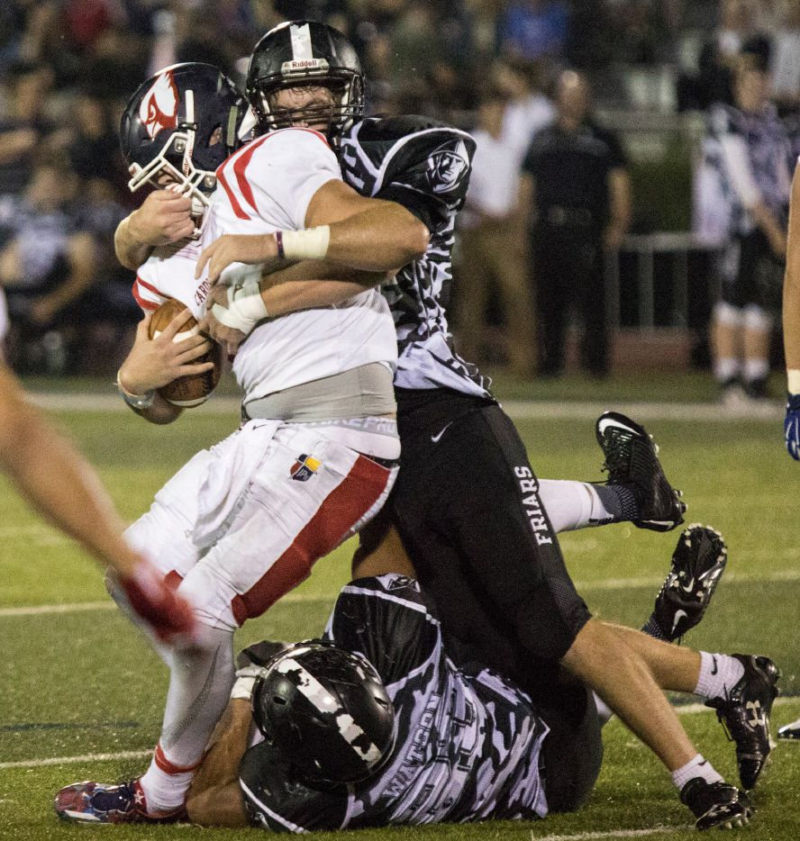 Bishop Lynch defensive lineman Warren Wall (50) brings down John Paul quarterback Austin Tyler (2) by the face mask during Bishop Lynch's matchup against John Paul II on Oct. 14, 2016, at Bishop Lynch High School in Dallas, Texas. (Andrew Buckley/Special Contributor)