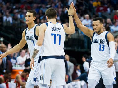 Dallas Mavericks forward Luka Doncic (77), guard Jalen Brunson (13) and forward Dwight Powell (7) celebrate at a timeout during the fourth quarter of an NBA game between the Dallas Mavericks and the New Orleans Pelicans on Monday, March 18, 2019 at American Airlines Center in Dallas.