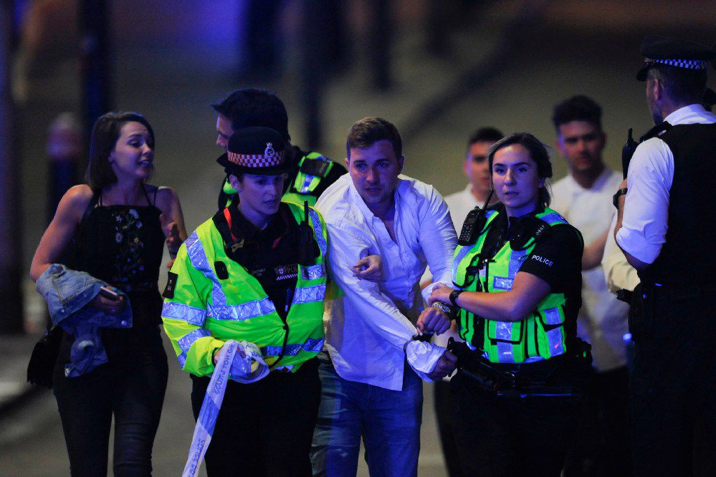 Police escort a member of public as they clear the scene of a terror attack on London Bridge in central London on June 3, 2017.